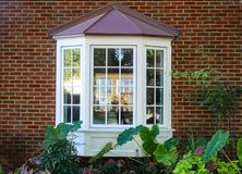 Bay window in a brick house with reflection of trees and view of windows and flowers inside and flowers and elephant ears outside. The Bay window in a brick stock photography