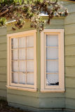 Bay window. Rotten bay window and pale green old wooden house Stock Photo