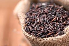 Baya del arroz del primer en saco en la tabla de madera Foto de archivo libre de regalías
