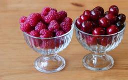 Baya roja de la frambuesa y de la cereza en bulto en bol de vidrio fotos de archivo
