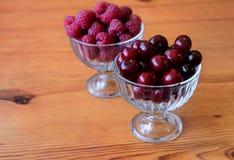 Baya roja de la frambuesa y de la cereza en bulto en bol de vidrio imagenes de archivo