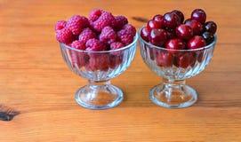 Baya roja de la frambuesa y de la cereza en bulto en bol de vidrio fotografía de archivo libre de regalías