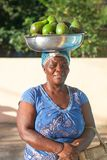 African woman with pelvis on her head with ripe green avocados royalty free stock photos