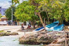 BAYAHIBE, DOMINICAN REPUBLIC - MAY 21, 2017: People are sitting by the shore. Copy space for text. BAYAHIBE, DOMINICAN REPUBLIC - MAY 21, 2017: People are stock images