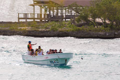 BAYAHIBE, DOMINICAN REPUBLIC - MAY 21, 2017: Tourists in a boat by the shore. Copy space for text. BAYAHIBE, DOMINICAN REPUBLIC - MAY 21, 2017: Tourists in a royalty free stock photos