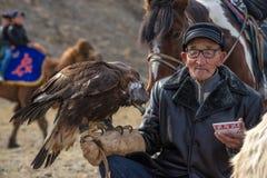 BAYAN-OLGII省,蒙古- 10月 01日2017年:传统蒙古鹫节日 未知的老蒙古人猎人Berk 免版税库存照片