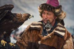 Bayan-Olgii, Монголия - 1-ое октября 2017: Фестиваль охотников с беркутами Портрет малознакомого монгольского охотника с Ber стоковые изображения