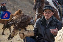 BAYAN-OLGII PROVINCE, MONGOLIA - OCT. 01, 2017: Traditional Mongolian Golden Eagle Festival. Unknown Old Mongolians Hunter   Berk. Utchi  With Golden Eagle And A Royalty Free Stock Photos