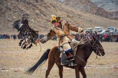 Bayan-Ulgii, Mongólia - 1º de outubro de 2017: Eagle Festival dourado Mongolian Hunter Berkutchi In Traditional Clothes com um E  Fotos de Stock