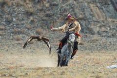 Bayan-Ulgii, Mongólia - 1º de outubro de 2017: Eagle Festival dourado tradicional O voo Eagle And Unknown Mongolian Hunter dourad fotografia de stock royalty free