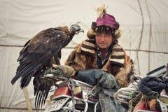 Bayan-Ulgii Mongolia, Październik, - 01, 2017: Ekspresyjny Mongolski myśliwy Berkutchi W Tradycyjnym Odziewa pozy Z Złotego eagle Fotografia Stock