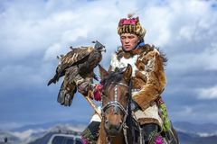 Kazakh man in traditional outfit with his eagle on a horse stock image
