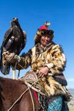 Kazakh Eagle Hunter Berkutchi with horse teaches his daughter to hunting to the hare with a golden eagles. BAYAN-ULGII, MONGOLIA - SEP 30, 2017: Kazakh Eagle Royalty Free Stock Photo