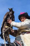 Kazakh Eagle Hunter traditional clothing, while hunting to the hare holding a golden eagle on his arm Royalty Free Stock Photos