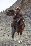 Kazakh Eagle Hunter traditional clothing, while hunting to the hare holding a golden eagle on his arm Stock Image