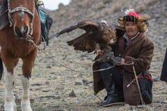 Mongolian Kazakh Eagle Hunter traditional clothing, holding a golden eagle on his arm Stock Photos