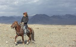 Kazakh eagle hunter traveling on hgis hotse in a landscape of altai Mountains stock photos