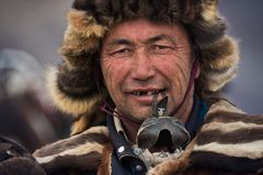 Bayan-Ulgii Mongoliet - Oktober 01, 2017: Guld- Eagle Festival Stående av okända mongoliska Hunter With Expressive Sight And Ru Royaltyfri Fotografi