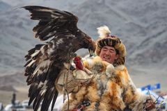 Bayan-Ulgii Mongoliet - Oktober 01, 2017: Mäktig mongolisk Hunter In Traditional Clothes Of rävpäls med en guld- Eagle On Han Royaltyfria Foton