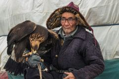 Bayan-Ulgii Mongoliet - Oktober 01, 2017: Traditionella guld- Eagle Festival Stående av pittoreska glasögonprydda gamla mongolisk Royaltyfria Bilder
