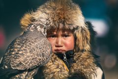 Bayan-Ulgii, Western Mongolia - October 07, 2018: Nomad Games, Golden Eagle Festival. Mongolian Boy With Offended Eyes Holding A B stock photography