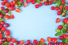 Bayas de fresas y cerezas y menta en un fondo azul Las banderas y las postales del concepto copian la opinión superior del espaci fotografía de archivo libre de regalías