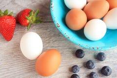 Bayas de la paja y bayas azules un cuenco verde por completo de huevos marrones y blancos Fotografía de archivo