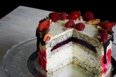 Bayas de la torta Torta increíblemente apacible de la semilla de amapola con crema agria, el confit de cerezas y de pasas y una c Imagen de archivo libre de regalías