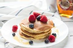 Bayas del desayuno Crepes Desayuno romántico en una tabla de madera Campo de la mañana del resorte? de la hierba verde y del ciel imagen de archivo