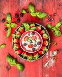 Bayas del verano con requesón, las hojas de la albahaca y la cuchara en fondo de madera rojo Imagen de archivo