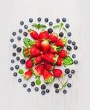 Bayas del verano: zarzamoras, arándanos, fresas, componiendo en el fondo de madera blanco, visión superior imagenes de archivo
