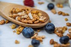 Bayas frescas y granola lleno de la pizca de la cuchara de madera, primer, selecto imágenes de archivo libres de regalías