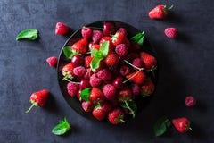 Bayas maduras rojas frescas en la placa negra Fotos de archivo