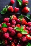 Bayas maduras rojas frescas en la placa negra Foto de archivo libre de regalías