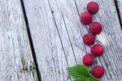 Bayas orgánicas frescas frambuesas en la tabla de madera vieja foto de archivo libre de regalías