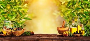 Bayas recién cosechadas de las aceitunas en los cuencos de madera y el aceite presionado imágenes de archivo libres de regalías