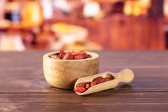 Bayas rojas secadas del goji con la cocina rústica fotografía de archivo