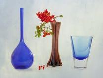 Bayas rojas y floreros azules fotografía de archivo