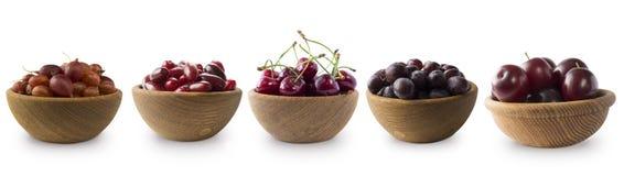 Bayas rojo oscuro en un fondo blanco Cerezas, grosellas espinosas, uvas y ciruelos en un cuenco de madera Foto de archivo libre de regalías