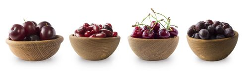 Bayas rojo oscuro en un fondo blanco Cornels, ciruelos, cerezas y uvas en un cuenco de madera Imagenes de archivo