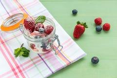 Bayas salvajes con el yogur en un tarro de cristal Visión desde arriba Fotos de archivo libres de regalías