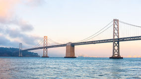 Baybridge av San Francisco på solnedgången Fotografering för Bildbyråer