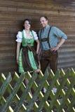 Bayerische Paare, die hinter einem Bretterzaun stehen Lizenzfreies Stockfoto