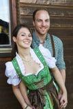 Bayerische Paare, die vor einem Holzhaus stehen Lizenzfreies Stockfoto