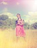 Bayerisches Mädchen trägt einen Dirndl und hält ein brezel Stockfotografie