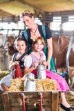 Bayernfamilie, die pushcard im Kuhstall fährt Lizenzfreie Stockbilder