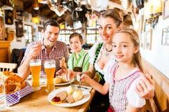 Bayersk familj i tyskt äta för restaurang Arkivbild