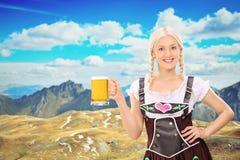 Bayersk kvinna som rymmer ett öl högt i bergen arkivbild