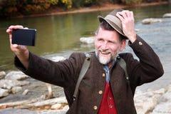 Bayersk man i hans 50-tal som står vid floden och tar en selfie Arkivbilder