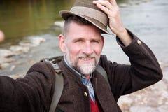 Bayersk man i hans 50-tal som står vid floden och tar en selfie Royaltyfri Bild